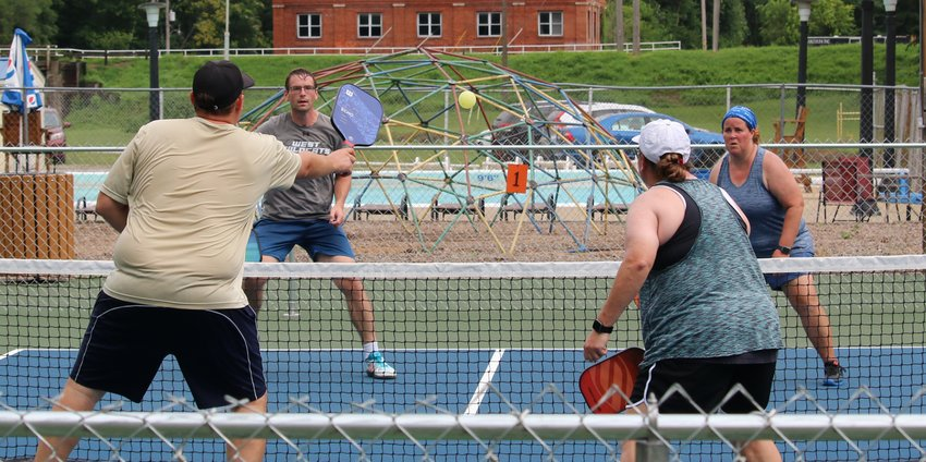 In the foreground, Josh Sander returns a shot during mixed doubles play with partner Tara Mata against Lynn Hanson and Christopher Shultz at the Central Park pickleball courts in Hillsboro. Hanson and Shultz would go on to take first in the 4.5 mixed doubles bracket, beating the team of Shelley Tischkau and Rod Robbins 17-15 in the final game.