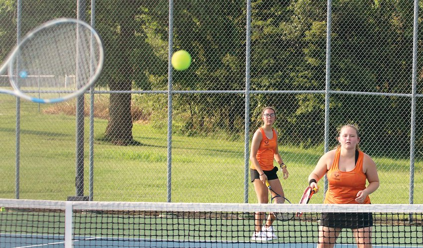 Hillsboro seniors Ruthie Mathews (left) and Macy Shipman wait to see the direction of the return from the Greenville side during their doubles match with Paige Mathias and Evie Johnson on Tuesday, Aug. 31. The match would be a tough one for the Toppers, who fell to their South Central Conference foes 9-0.
