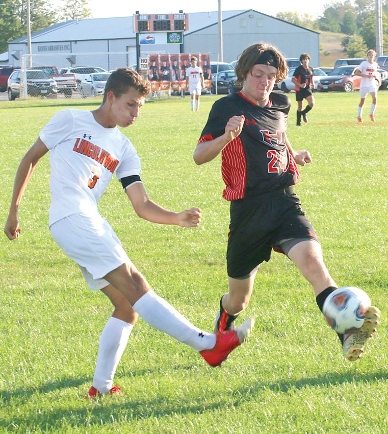 Hillsboro's Matt Page (in black) gets a foot on Levi Weir's shot during the second half of the Toppers' home game against Lincolnwood on Monday, Sept. 20. The two seniors resulted in the only two goals of the 1-1 tie between the two rivals.