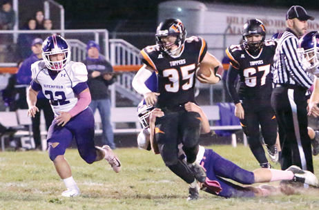 Hillsboro's Drew Willman (#35) tries to shake free from the grasp of a Panther defender during the Toppers' final game of the season against Litchfield on Friday, Oct. 19. Hillsboro would pick up a 51-6 victory over the Purple Panthers to end their season with a 3-6 mark.