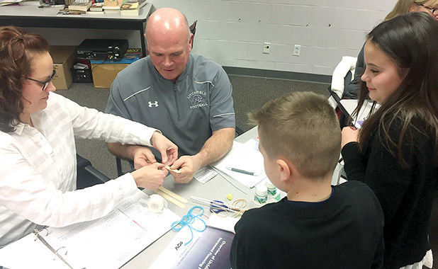 Russell Elementary School fourth graders Sam Schwab and Darby Braasch, work with Litchfield School Board members Jen Reid and Ron Anglin on an engineering project to create a pom pom launcher at the meeting Thursday evening, March 15, at Litchfield High School.