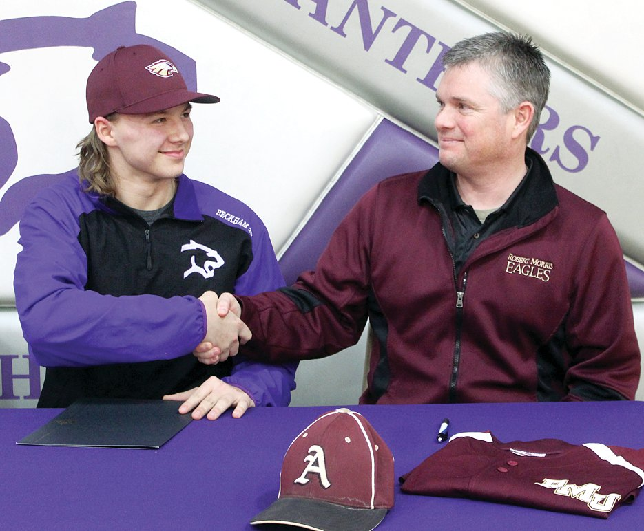 Litchfield senior Billy Beckham is congratulated by Robert Morris College Baseball Coach Chris Hostettler after signing his letter of intent to play baseball for the Eagles after graduation.