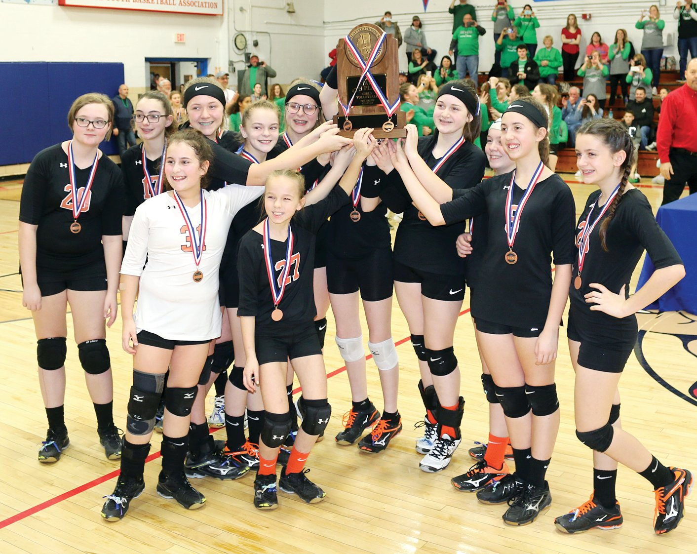 Members of the Lincolnwood Junior High seventh grade volleyball team celebrate with their fourth place trophy after their final game at the IESA Class 2A State Tournament on Saturday, March 9, in Pawnee. The Lady Knights capped off a spectacular season with a 24-7 record and the second IESA volleyball state trophy in the school's history.