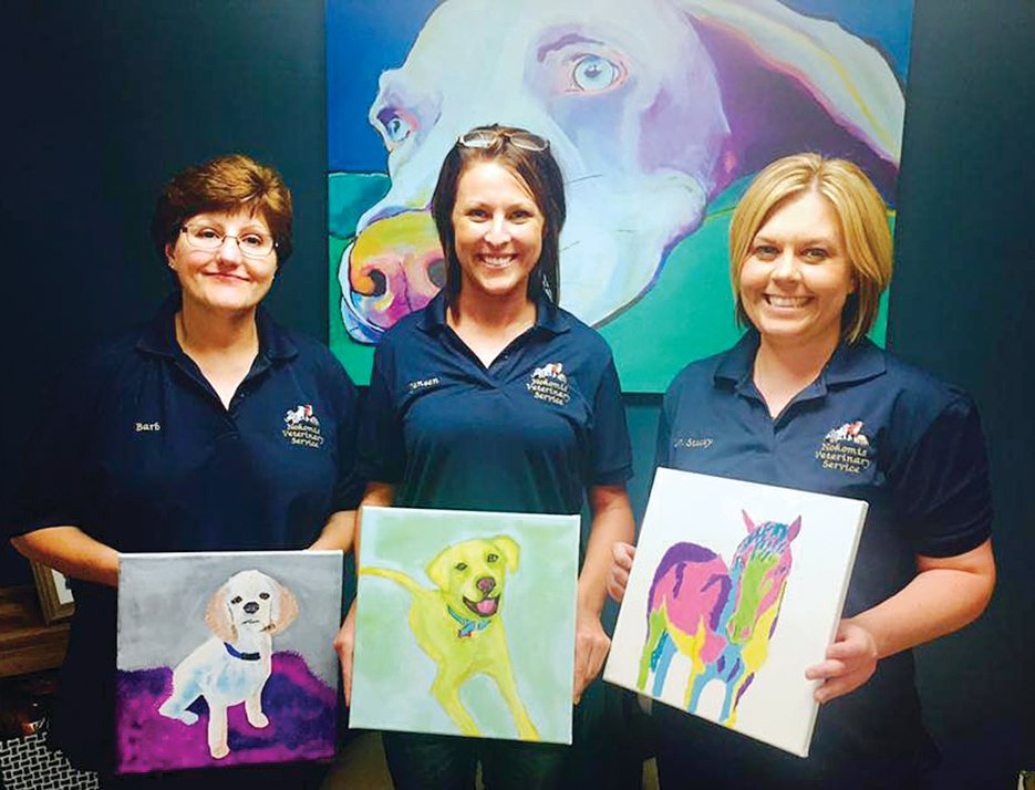 From left, Barb Meiners, Jensen Patton and Dr. Stacey Funderburk with examples of Paint Your Pet portraits.