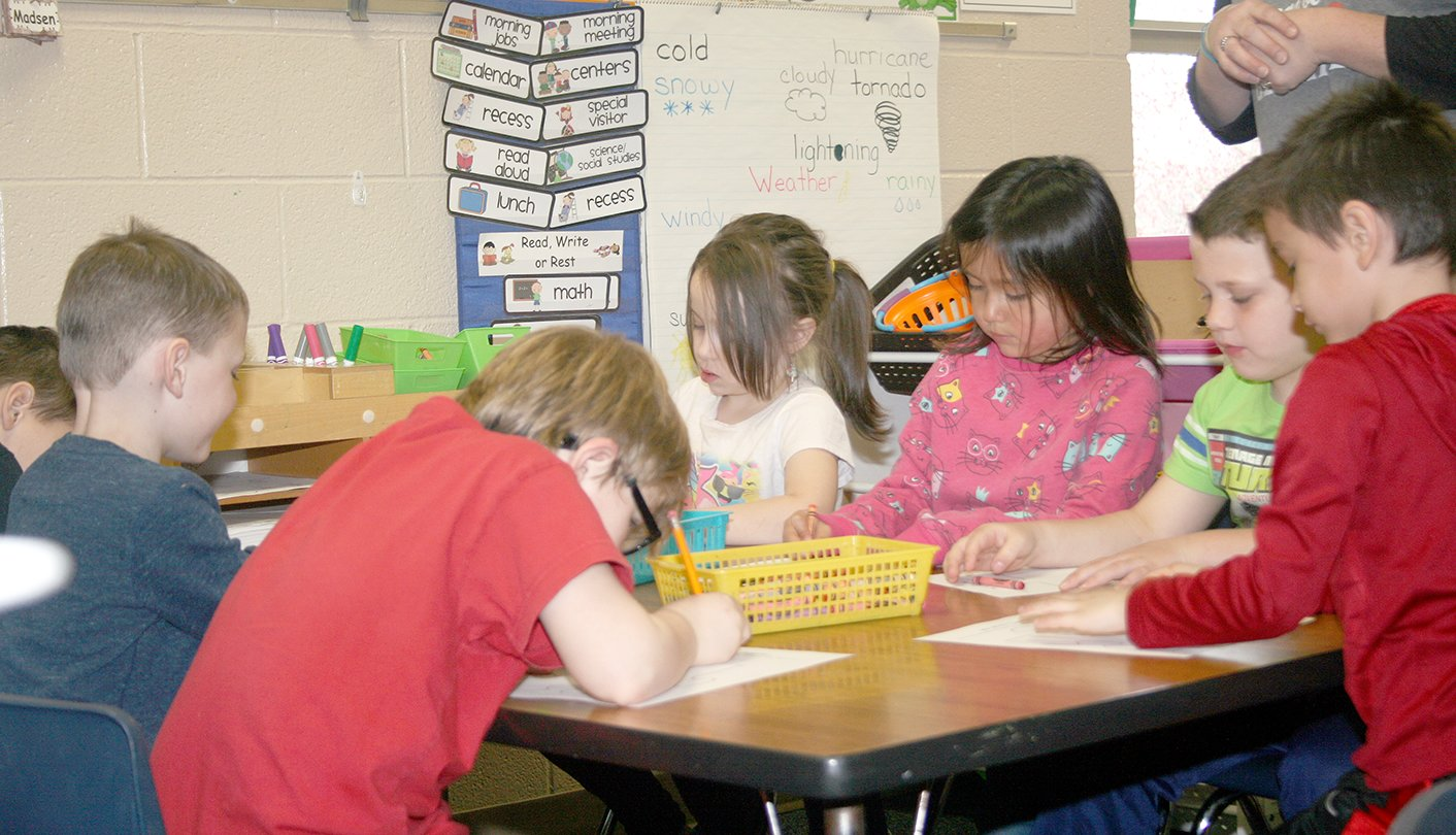 Kindergarten students Owen Lanthrip, Hayden Werner-Long, Sophia Hughes, Catalaya Baxin, Carson Summers, and Silas Gutierrez studiously decorate puzzle piece worksheets in recognition of autism awareness month.