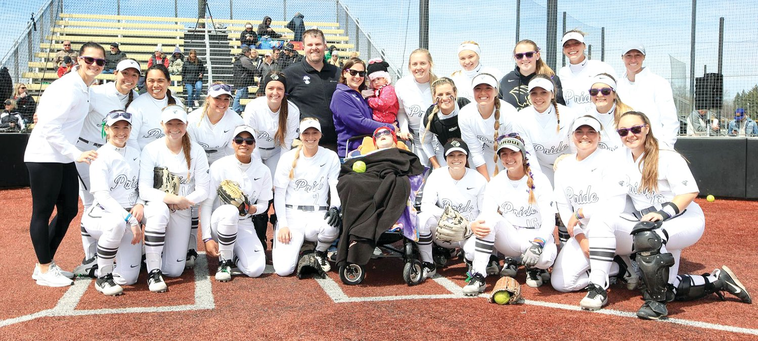 Members of the Purdue Northwest University softball team welcomed seven-year-old Grace Herschelman of Hillsboro and her family to the Pride's game on Saturday, April 13, for the third annual Grace Filled Journey game. To Grace's right is Tessa Steffens of Litchfield, who had three hits and scored twice in the Pride's two wins over Ferris State on the day and caught the ceremonial first pitch by Grace's two-year-old sister Charlotte.