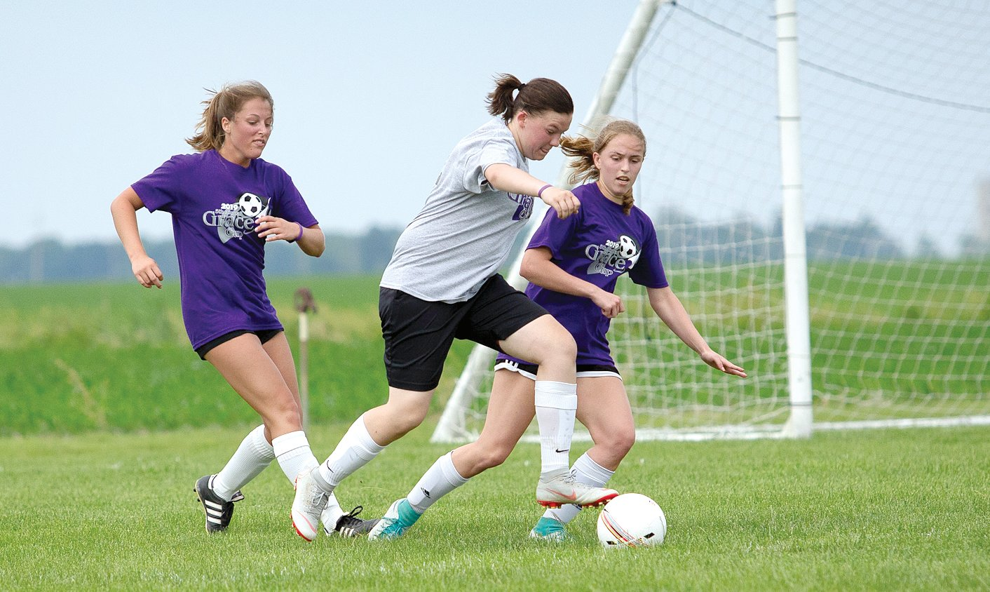 Hillsboro's Aubry Rupert takes on two defenders during the Grace Cup on Saturday, June 8, at Terry Todt RHSA Field in Raymond. Rupert, one of five players from Hillsboro to take part in the charity all-star game, scored a goal in the Gray team's 3-2 victory over the Purple team.