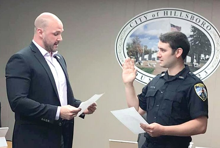 Hillsboro commissioner Michael Murphy, at left, swears in Adam Fath as the newest member of the Hillsboro Police Department on Tuesday evening, June 11.