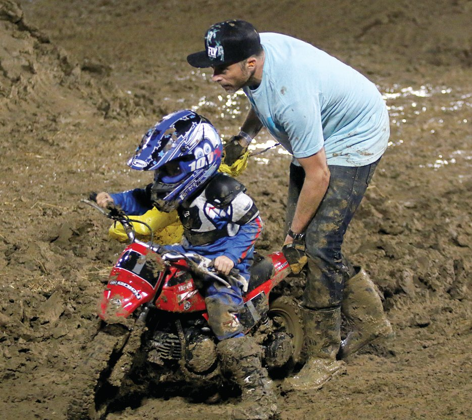 Jacob Cox gets a little help during the 50 beginner class at the Montgomery County Fair motocross races on Friday, June 21.