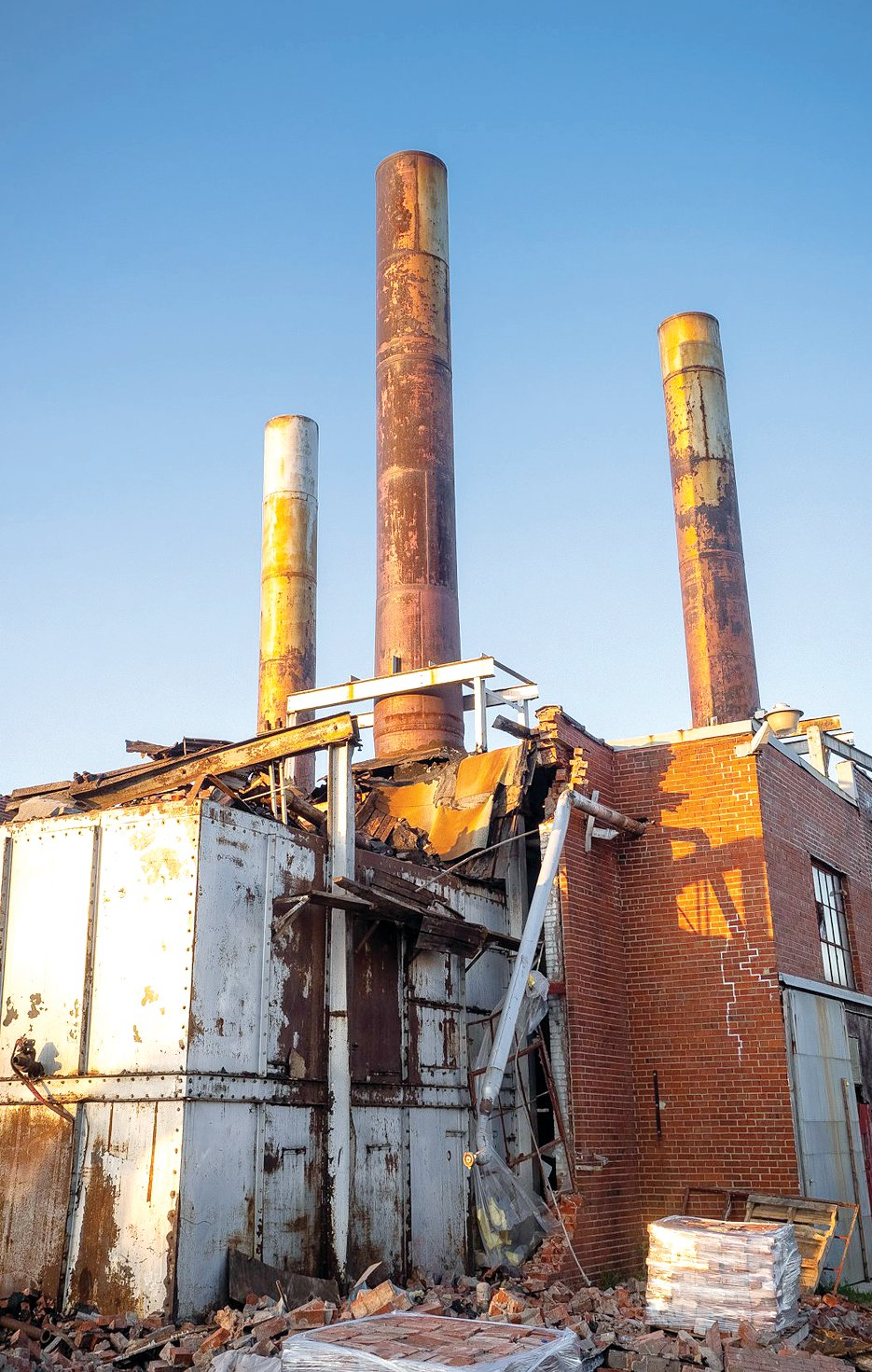 Smokestacks from the Litchfield Creamery building jut into a cloudless blue sky earlier in the demolition process. The stacks are now down, with the salvageable material shipped away for recycling.