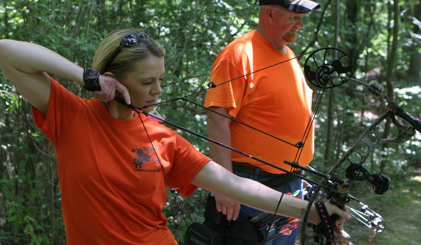 Kristen Warren of Livingston takes aim at a target while her father Dave Lindsay of Litchfield watches at the Deer Tales Cancer Shoot on Sunday, July 14.