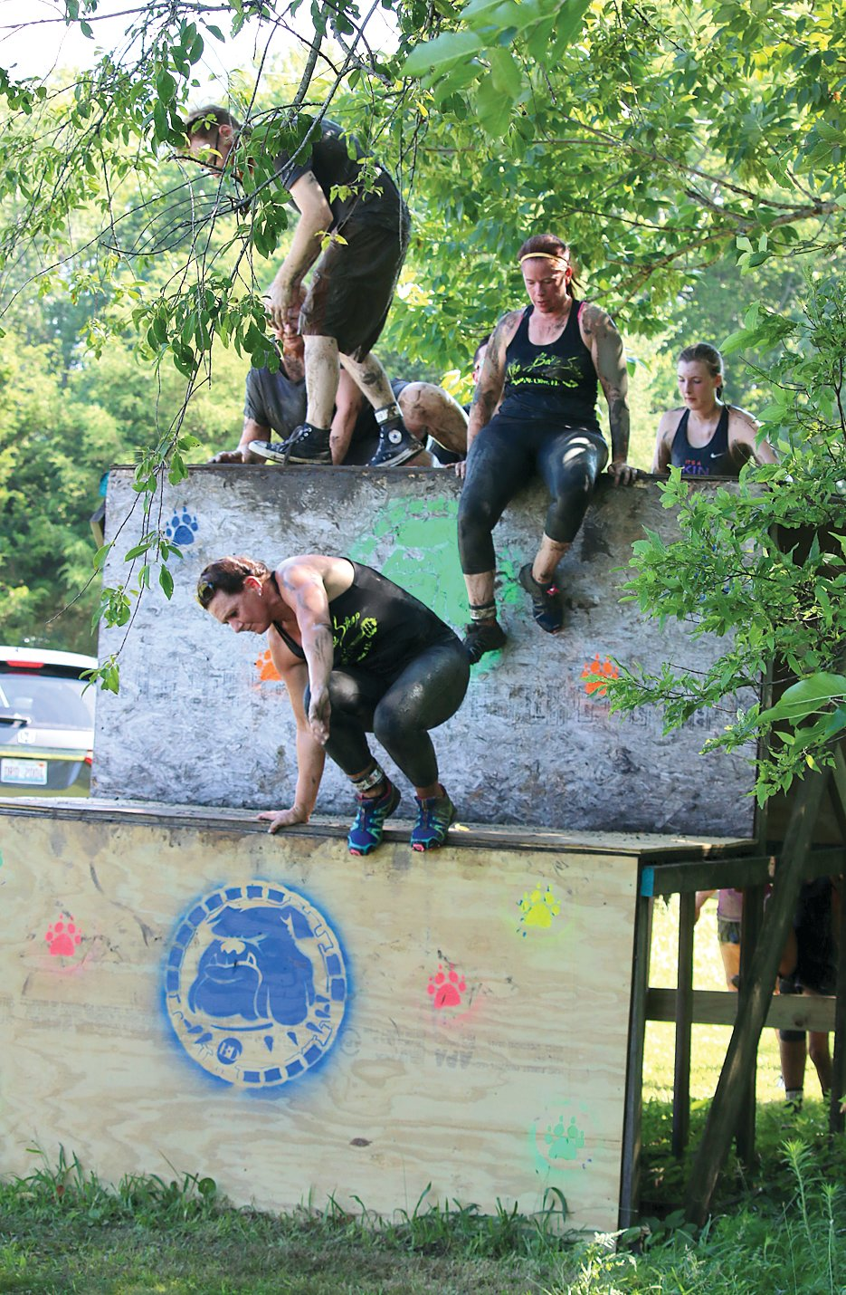 With the finish line in site and exhausted from the previous three miles of the water, hill and mud filled Big Dawg Dare course, runners climb over handmade obstacles near the end of the 5K route.