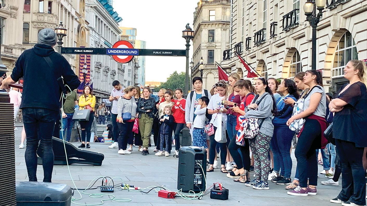 Students from Litchfield High School experience the local sound of London from a busker performing at Picadilly Circus during their tour of France and the United Kingdom.