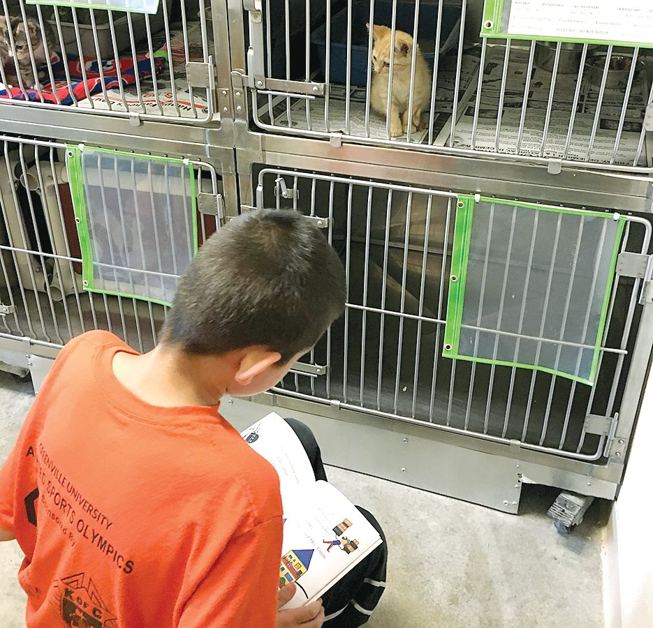 Above, a local student, Brandon, reads to a furry friend at the Montgomery County Animal Control Shelter