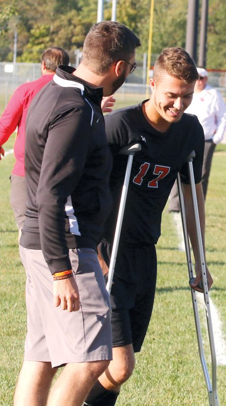 Hillsboro's Dalton Greenwood shares a smile with Coach Jason Burke after coming off the field seconds after kickoff on Tuesday, Oct. 8. Greenwood, who suffered a season ending knee injury against Carlinville, started the game, which was senior night for him and ten other Toppers.