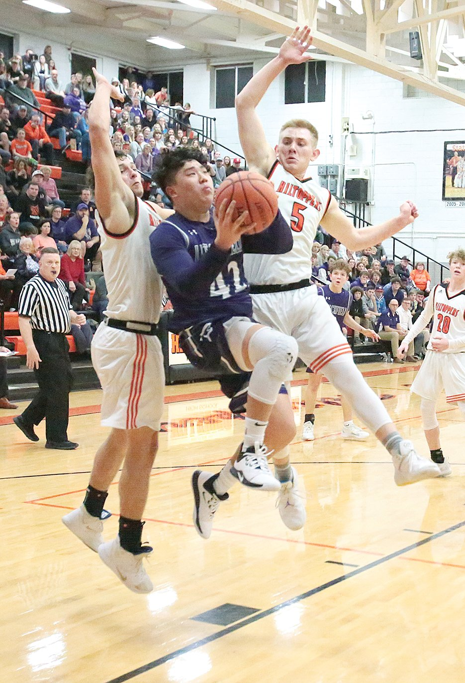 Hillsboro's Nic Ondrey (left) and Jace Tuetken (right) try to impede John Corso's path to the basket during the Toppers' game against Litchfield on Friday, Feb. 21. Corso would put in a game-high 25 points in the Panthers' 61-60 win over the Hiltoppers.
