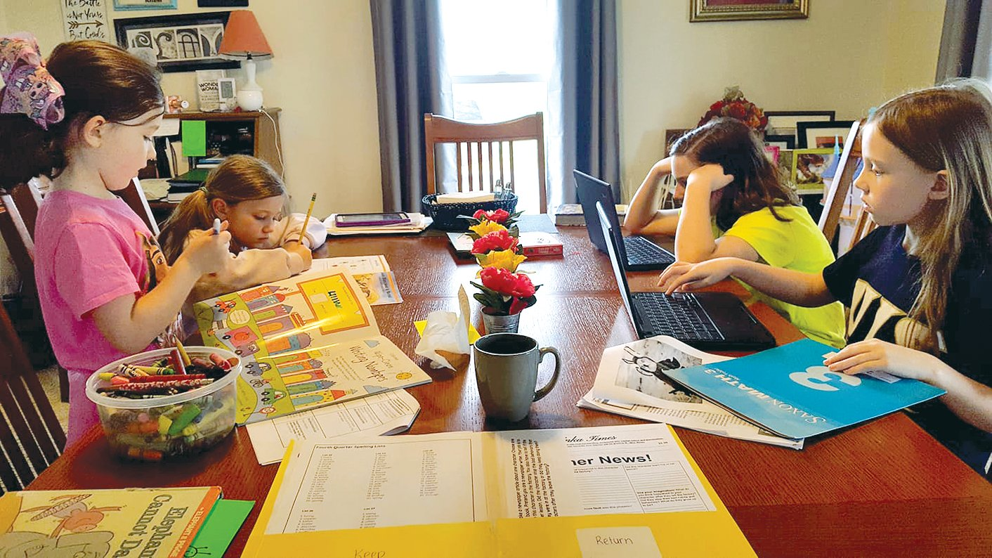 The Beeler sisters of Raymond, who attend Zion Lutheran School in Litchfield, spend time working remotely from their kitchen table. From the left are Lil Beeler, Josie Beeler, Kate Beeler and Nora Beeler.