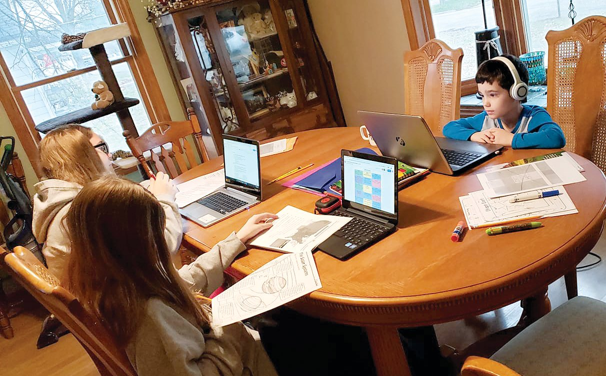 The Christian family of Hillsboro spends each morning during school time doing remote learning activities around the family table. From the left are Hailey Christian, Bailey Durbin and Colton Christian as they do school work at home. Students all across Montgomery County have been participating in remote learning activities since March 16.