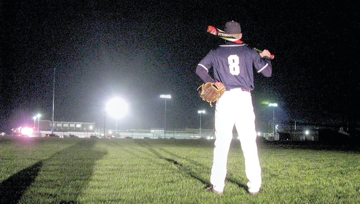 "Litchfield senior Clayton Walch looks across the darkened Plummer-Tiemann Field at Litchfield High School toward the football field he played on for four years, Lloyd J. Hill Field, lighted in full regalia as a tribute to the class of 2020 during the Lights For The Fight show of support on Friday, April 17. Walch was poised to be a crucial part of the Panthers' baseball team this fall, but with the cancellation of school due to the COVID-19 pandemic, odds are slim Litchfield will take the field. ""For a dad that had watched him grow and progress through summers of little league and his three high school seasons so far, it is tough to see it come to an abrupt end,"" said Clayton's father Curt, who took the photo."