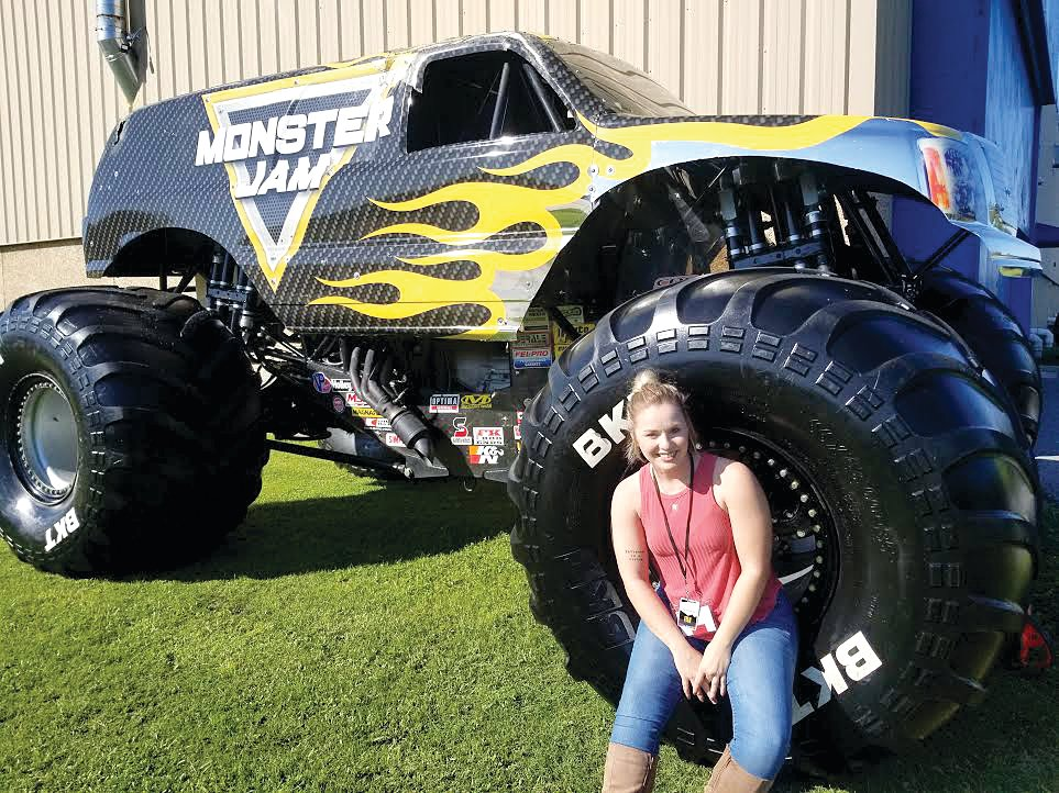Montgomery County native Becca Marsch (above) takes a quick moment to pose with one of the monster trucks that will appear at the parties she organizes as a pit party coordinator with Monster Jam.