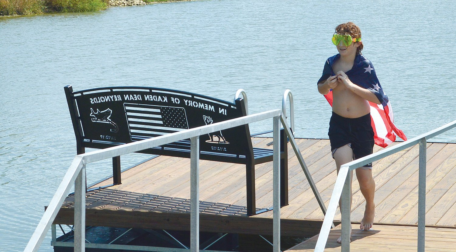 Konnor Reynolds, brother of the late Kaden Reynolds of Nokomis, christened a dock and benches in his big brother's honor with a jump into the pond at Rountree Gun Club.