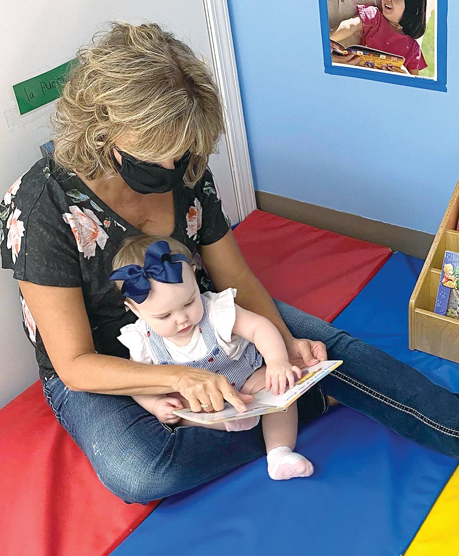 Shelly Fenton of Hillsboro Community Child Devleopment Center uses a mirror to interact with Rowan Reitz. One way to help with brain development is to encourage the baby to follow the mirror and talk about body parts, like the nose, mouth and eyes.