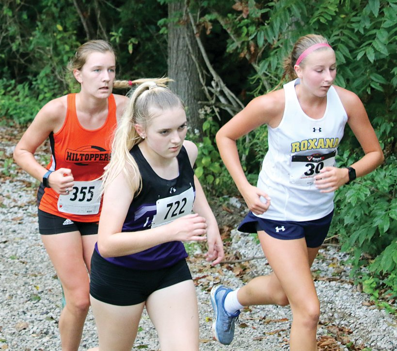 Hillsboro's Avery Smith and Litchfield's Kylee Eiting, along with Macie Lucas of Roxana, make their way up the hill and out of the woods of Loveless Park during the cross country meet in Carlinville on Tuesday, Sept. 1. Smith would set a personal best at the race, running a 24:47, while Eiting ran a 25:04 for the Panthers, who finished third as a team.