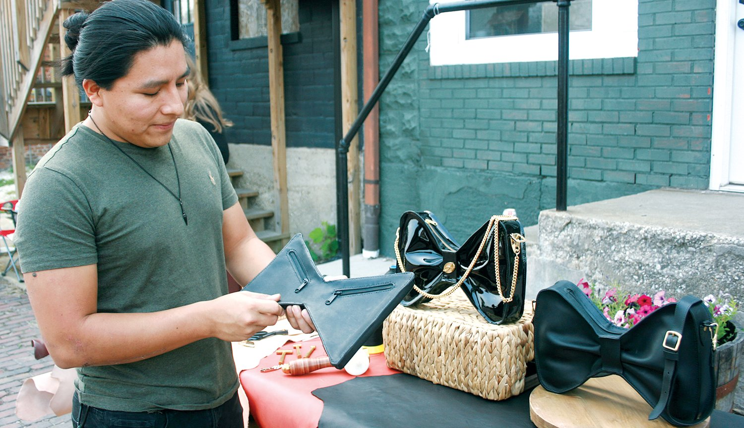 Alexandrea, a company that sells high-end handbags, will open a storefront in downtown Hillsboro. Owner Alex Haxel personally designs the bags her company will sell, and plans to debut her new line later this year. Leatherworker Edgar Gua (above) shows an early prototype of the Bow Bag. The finished prototype can be viewed at left, in the background of the photo.