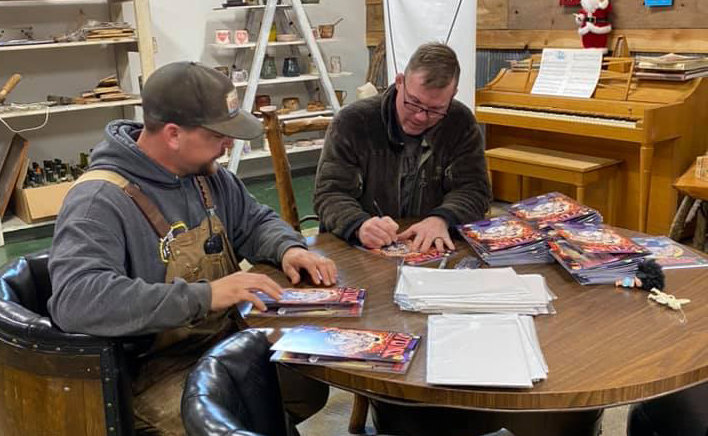 Chris Hubbart (left) and Matt Hughes (right) sign copies of Nathan Rosario's revised version of Stump. The comic book is set in Hillsboro and features characters based on both Hughes and Hubbart.