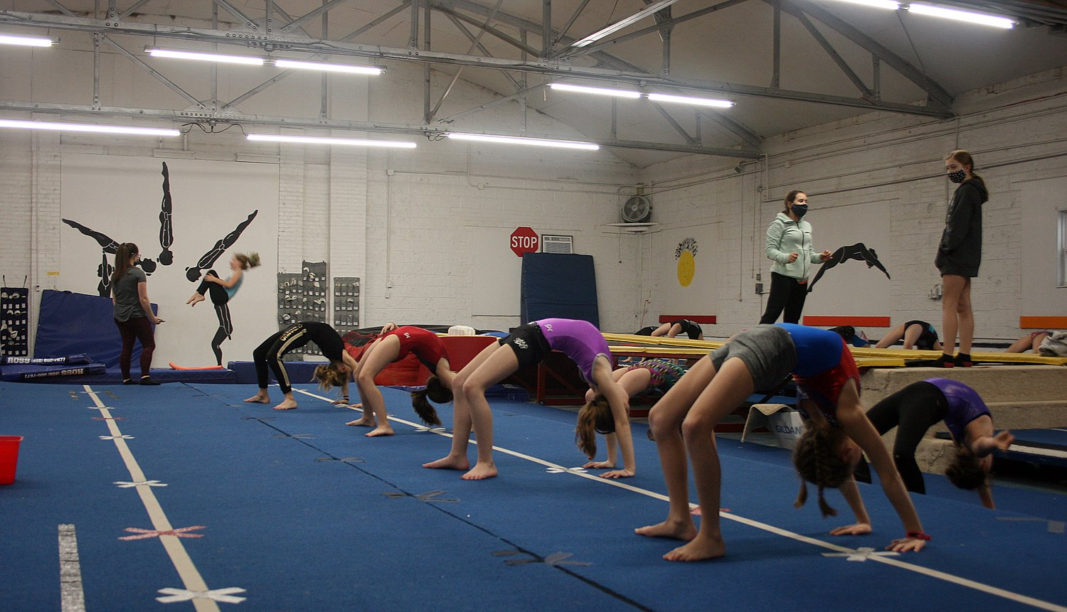 Hilltop Elite Academy of Tumbling and Trampoline, Inc., has been able to reintroduce their athletes back into the gym with COVID-19 safety precautions in place. Above, junior coaches Summer Spencer (masked, left) and Amya Greenwood (masked, right) lead stretching in the mid-level (advanced beginner to novice levels) class while Hannah Huber coaches an athlete on the trampoline in the background.