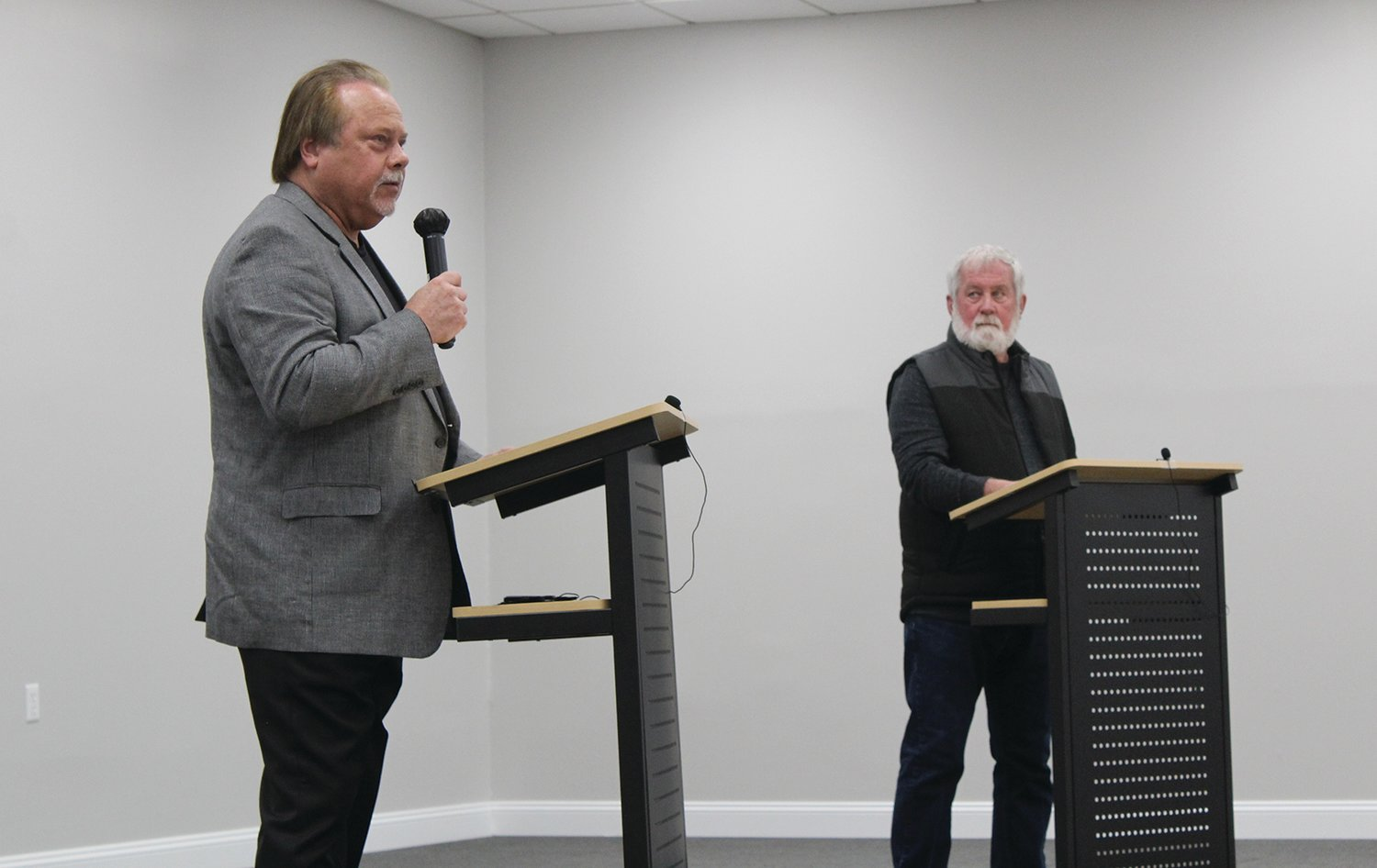 Candidates for mayor Steve Dougherty, at left, and Dwayne Gerl, at right, take the stage at the Litchfield Chamber of Commerce political forum held Tuesday evening, March 23, at the Litchfield Community Center.