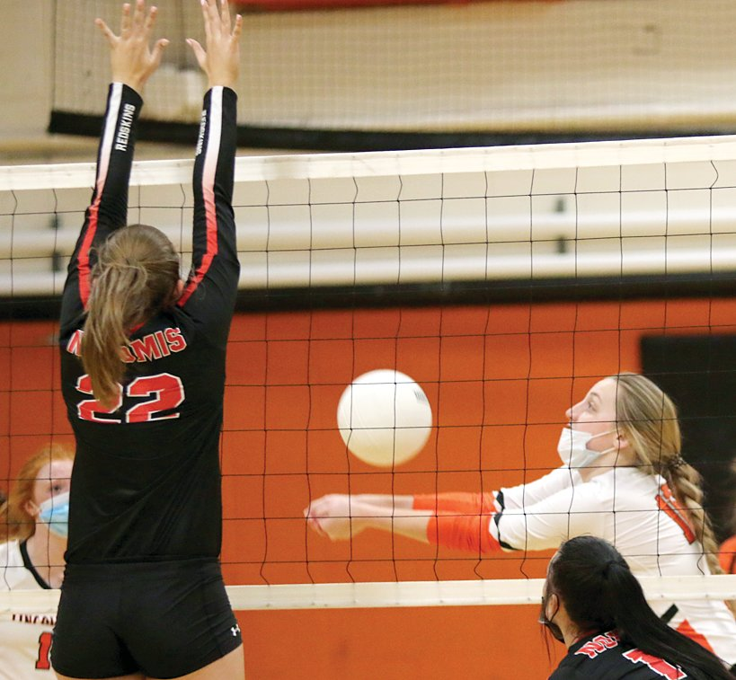 Nokomis' Skylar Stewart puts up some resistance as Katelyn Payne of Lincolnwood gets under a ball during the intra-county squabble in Raymond on Tuesday, April 6. Payne and the Lancers would score their ninth win of the season with a 25-10, 256 victory over the visiting Redskins.