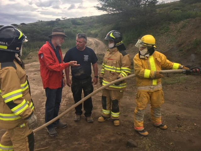 Translator Kevin Bruce explains a technique that Pat Boggs (in t-shirt) helped train firefighters in Ecuador earlier in the week during a mission trip.