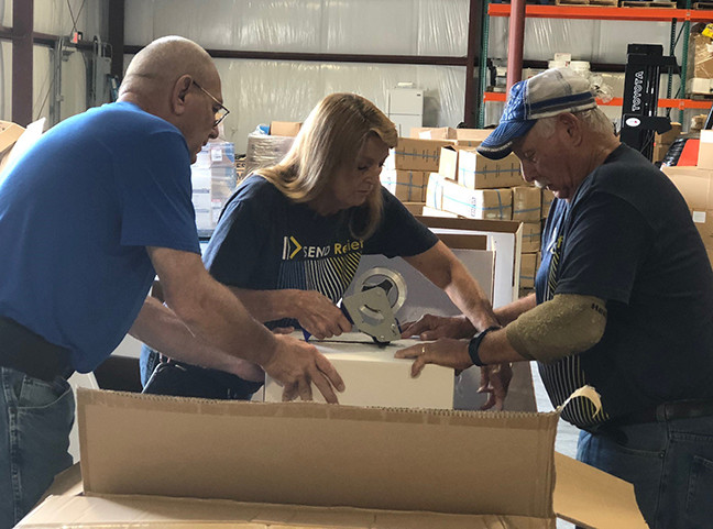 From left, Bob Perdue, Bonnie Prince and Jerry Ellis work at the Send Relief Appalachian Ministry Center in Cannonsburg, Ky., packing up items destined for the Carolinas and Virginia for hurricane relief work. (Kentucky Today/Mark Maynard)