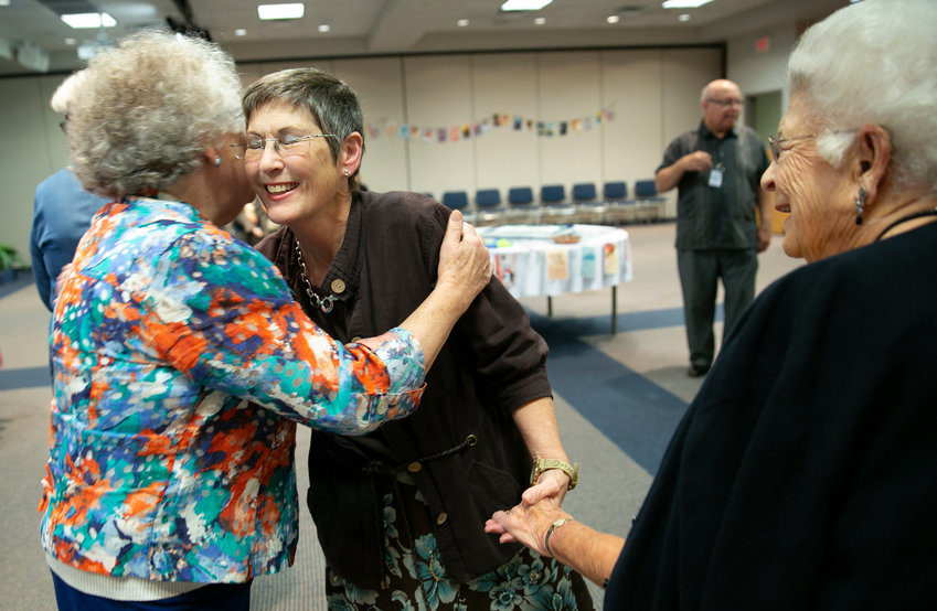 Joy Bolton is greeted with hugs at a retirement reception honoring her 19-year leadership of the Kentucky Woman's Missionary Union. Among the wellwishers were Nancy Polhill, left, and Peggy Hicks, co-directors of Lyndon Baptist Church WMU in Louisville, Ky.  Hicks was president of Kentucky WMU when Bolton was hired nearly two decades ago. (Kentucky Today/Robin Cornetet)