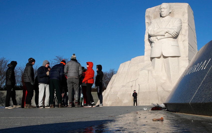 With a slick of ice in the foreground, people visit the Martin Luther King, Jr. Memorial, on MLK Day, Monday, Jan. 21, 2019, in Washington. (AP Photo/Jacquelyn Martin)