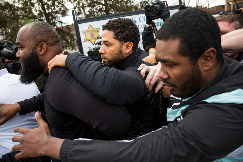 """Empire"" actor Jussie Smollett, center, leaves Cook County jail following his release, Thursday, Feb. 21, 2019, in Chicago. Smollett was charged with disorderly conduct and filling a false police report when he said he was attacked in downtown Chicago by two men who hurled racist and anti-gay slurs and looped a rope around his neck, a police official said. (Ashlee Rezin/Chicago Sun-Times via AP)"