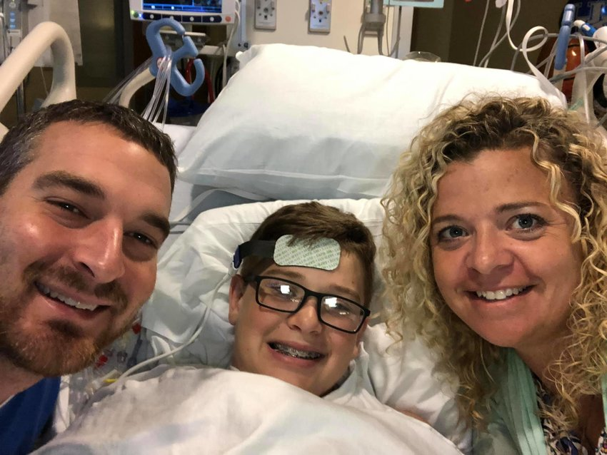Faithful Kentucky Baptists Derrick and Amy Burton are all smiles with son William, who survived a cardiac arrest on Tuesday at a Little League field (Amy Burton's Facebook page photo)