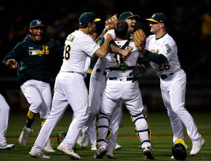 Oakland Athletics' Mike Fiers, center, celebrates with Matt Olson (28) Chad Pinder (18) and Matt Chapman (26) after pitching a no hitter against the Cincinnati Reds at the end of a baseball game Tuesday, May 7, 2019, in Oakland, Calif. (AP Photo/Ben Margot)