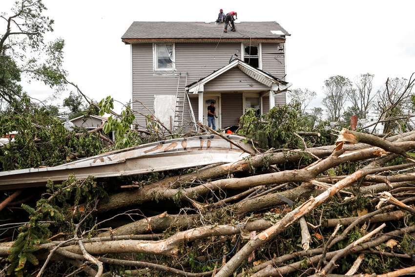 Workers work on a damaged home, Wednesday, May 29, 2019, in Dayton, Ohio, as cleaning efforts begin in a neighborhood damaged by a tornado storm system that passed through the area on Monday. Tens of thousands of Ohio residents were still without power or water in the aftermath of strong tornadoes that spun through the Midwest. (AP Photo/John Minchillo)