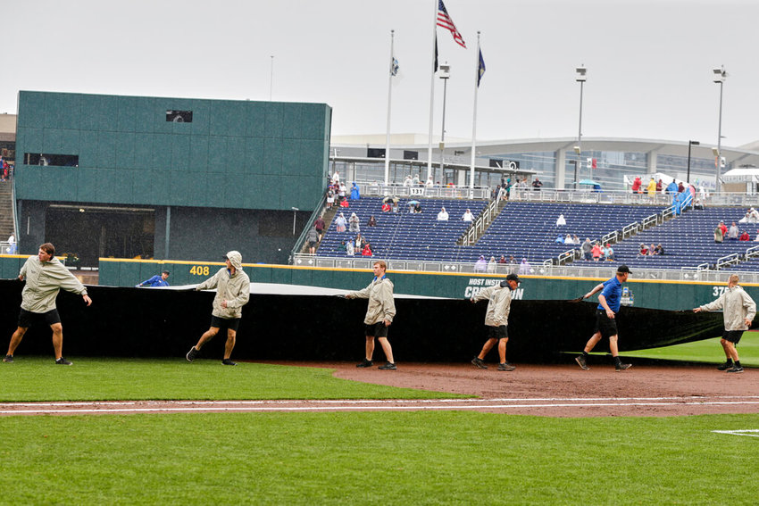 Groundskeepers roll out the tarp during a rain delay in an NCAA College World Series baseball game between Auburn and Louisville, in Omaha, Neb., Tuesday, June 18, 2019. (AP Photo/Nati Harnik)