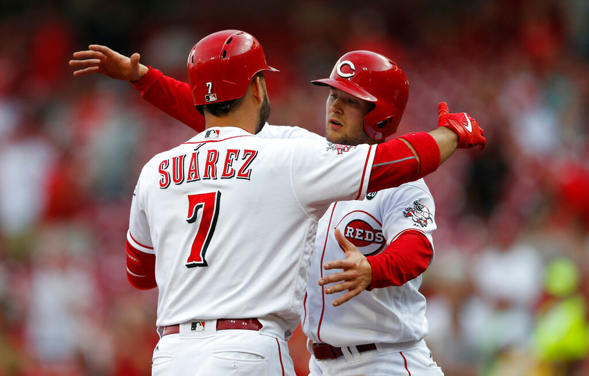 Cincinnati Reds' Eugenio Suarez (7) is greeted at home plate by Nick Senzel, right, following a two-run home run off Milwaukee Brewers starting pitcher Chase Anderson during the first inning of a baseball game, Tuesday, July 2, 2019, in Cincinnati. (AP Photo/Gary Landers)