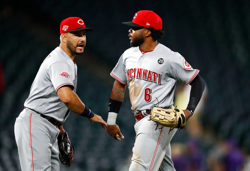 Cincinnati Reds third baseman Eugenio Suarez, left, congratulates left fielder Phillip Ervin after the ninth inning of a baseball game against the Colorado Rockies Saturday, July 13, 2019, in Denver. The Reds won 17-9. (AP Photo/David Zalubowski)