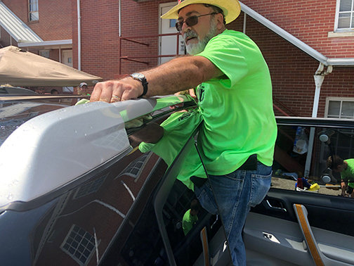 Randy Hennecke wipes down the top of a vehicle during the free car wash at the Greenup Baptist Association's All In event on Saturday. (Kentucky Today/Mark Maynard)