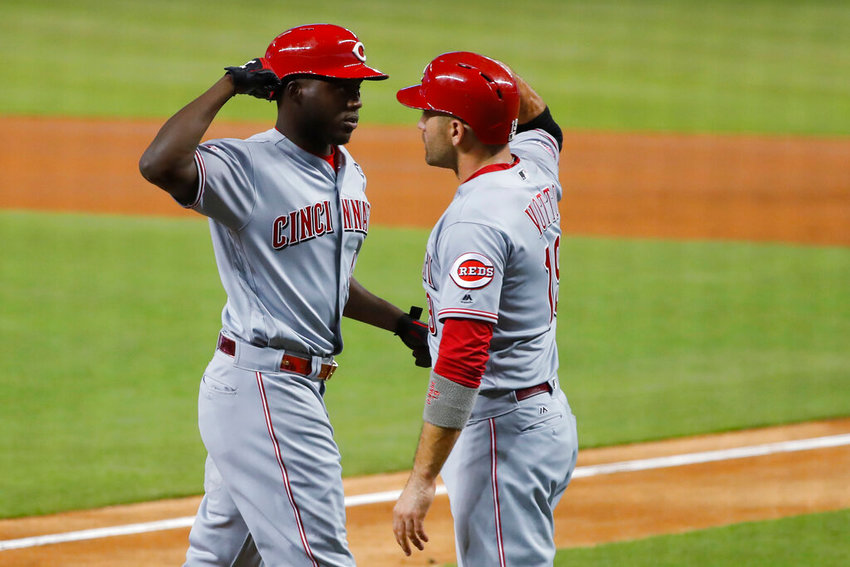 Cincinnati Reds' Aristides Aquino, left, is congratulated by Joey Votto after Aquino hit a hone run, scoring Lotto, during the first inning of the tema's baseball game against the Miami Marlins, Thursday, Aug. 29, 2019, in Miami. (AP Photo/Wilfredo Lee)