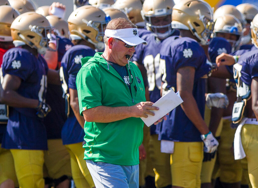 Notre Dame head coach Brian Kelly  looks at notes during NCAA college football practice, Thursday, Aug. 8, 2019, at the Culver Academies in Culver, Ind. (Robert Franklin/South Bend Tribune via AP)