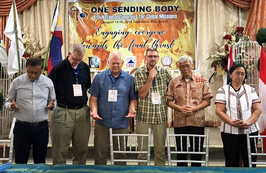 John Brady, the IMB's vice president of global engagement, prays during the Fourth National Congress for Global Missions in the Philippines. At the congress, the IMB signed a partnership covenant with One Sending Body (OSB), the sending entity of five Baptist conventions in the Philippines. Pictured (left to right): Pastor James Fundar, OSB president; Todd Lafferty, IMB executive vice president; John Brady; Jess Jennings, IMB leader for the Philippines; Pastor Lino Caronongan, chair of OSB; Precy Caronongan, OSB secretary. (IMB photo)