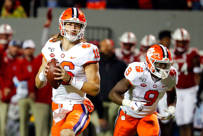 Clemson's Trevor Lawrence (16) prepares to throw the ball with teammate Travis Etienne (9) nearby during the first half of an NCAA college football game in Raleigh, N.C., Saturday, Nov. 9, 2019. (AP Photo/Karl B DeBlaker)