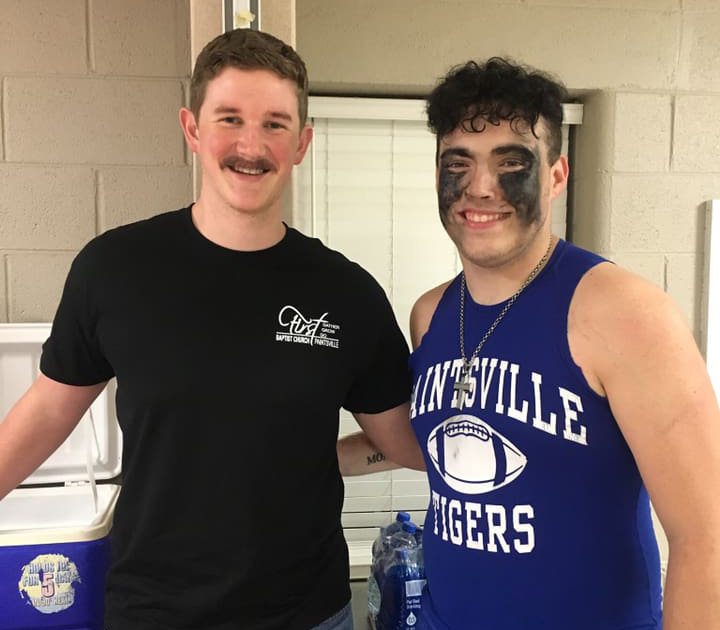 Seth Carter, the pastor of First Baptist Church in Paintsville, stands with Brandon Richmond during a post-game celebration last season. Carter is in his third year as chaplain of the Paintsville High School football team.