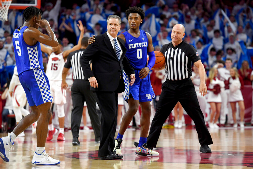 Kentucky players Ashton Hagans (0) and Immanuel Quickley (5) walk with head coach John Calipari, center, as he heads to the locker room after being ejected during the second half of an NCAA college basketball game against Arkansas, Saturday, Jan. 18, 2020, in Fayetteville, Ark. (AP Photo/Michael Woods)